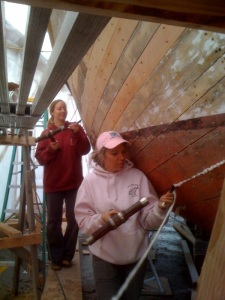 Volunteers Marnie Leist and Ginger Duncan learning to cork the hull of the salmon seiner Thelma C at an Ocean Bay Marine class at the Kodiak Maritime Museum. Photo courtesy of Brian Johnson & the Kodiak Maritime Museum.