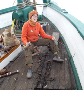 Boatwright Christine Jacobson reefing out seams on Northwest Seaport's 1889 tugboat Arthur Foss. Photo by Northwest Seaport.